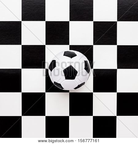 soccer ball on chequered black and white pattern