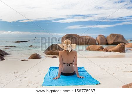 Woman wearing black bikini and beach hat, sunbathing at Anse Lazio beach on Praslin Island, Seychelles. Summer vacations on picture perfect tropical beach concept.