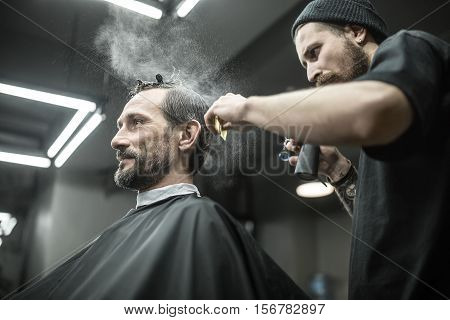 Fashionable man with a beard in the black cutting hair cape in the barbershop. Brutal barber splashes from the spray bottle at his hair. Hairdresser also has a cutting comb and scissors. Horizontal.