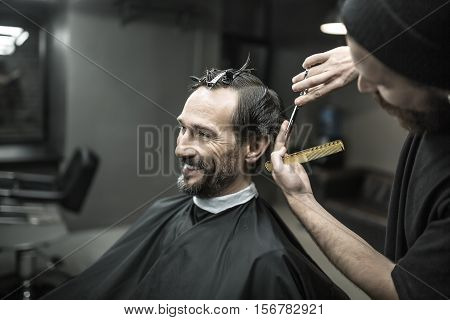 Smiling bearded man in the black cutting hair cape in the barbershop. He has hairgrips on his head. Barber in a black T-shirt and a cap is cutting his hair with scissors and a hair comb. Horizontal.