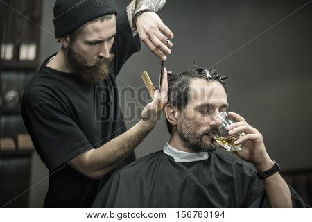 Brutal bearded man with closed eyes drinks whiskey from the glass in the barbershop. He is in the black cutting hair cape. Barber is cutting his hair with help of scissors and a hair comb. Horizontal.