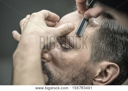 Bearded man in the barbershop. Barber is trimming his hair with a straight razor. Closeup. Horizontal.