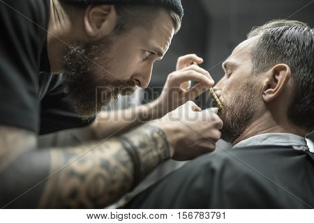 Clever bearded barber is trimming the beard of his client in a black cutting hair cape in the barbershop. He is using a cutting comb and a hair clipper. Customer sits with closed eyes. Closeup.