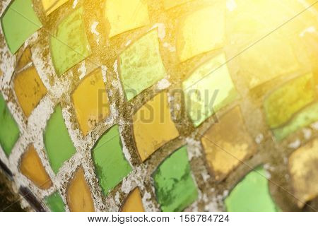 closeup of reflect sunlight toThai ancient dragon's scaly stucco and color glass in temple abstract texture background.