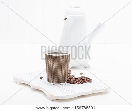 Fresh black coffee served in a brown disposable paper cup.