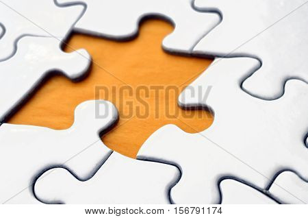 A close up view of a white jigsaw puzzle with a single piece missing.