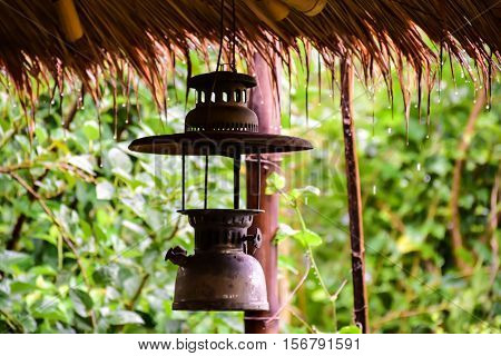 Hurricane lamp is hang under eaves on the raining day.