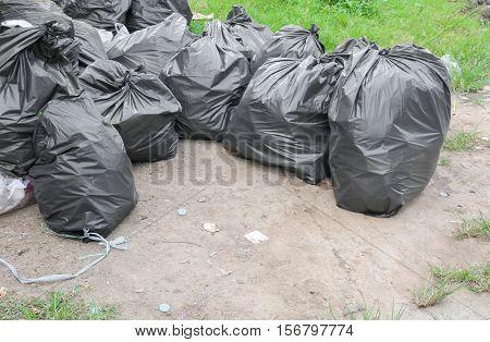 Pile of black garbage bag unsanitary  roadside .