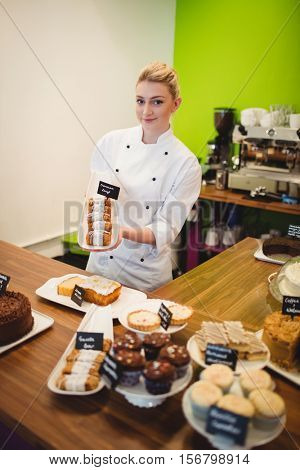 Portrait of worker holding sweet food at counter in cake shop