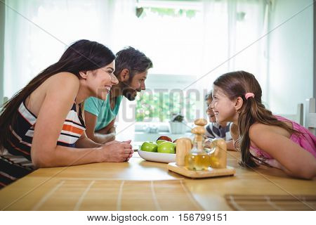 Parents and kids looking face to face and smiling at the dinning table