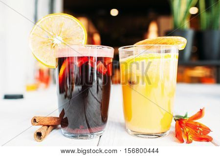 Two glasses of hot mulled wine on restaurant table. Hot yellow and red grog with orange. Tasty Christmas drink, seasonal beverage, date, party, relaxation concept