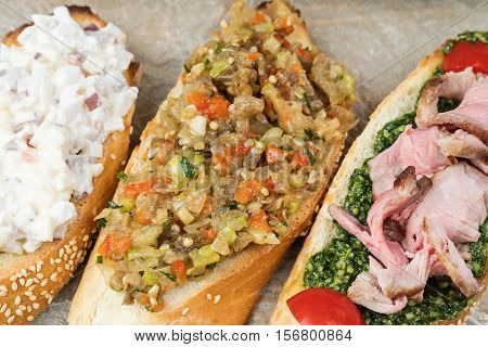 Three different delicious sandwiches close up lying on paper