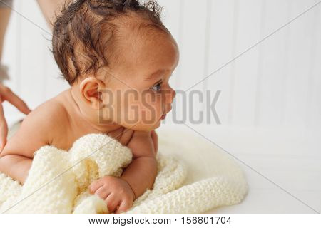 Newborn baby on stomach looking aside, free space on white. Adorable little child interested of something. Background for children care and development products