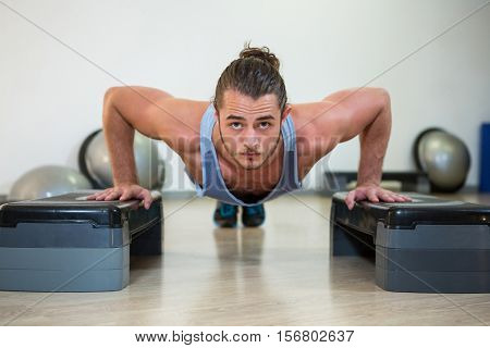 Portrait of man doing aerobic exercise on stepper in fitness studio