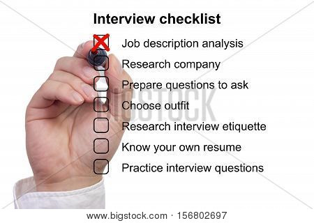 Hand crosses off the first item on a preparation checklist to prepare for job interview