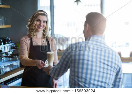 Waitress serving a cup of cold coffee to customer Waitress serving a cup of cold coffee to customer in cafe