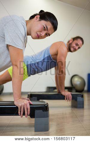Portrait of two men doing aerobic exercise on stepper in fitness studio
