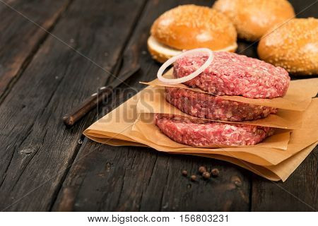 Raw ground beef meat burger steak cutlets on dark wooden table with copy space