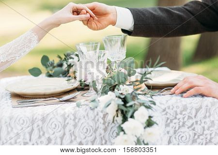 Couple holding hands above served table. Groom help his bride to stand up. Love, etiquette, care concept