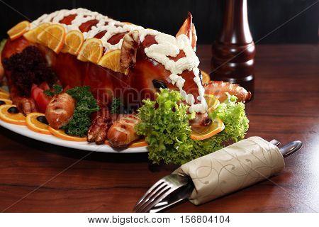 Roast suckling pig decoration with vegetables on big plate