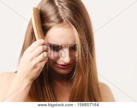 Woman refreshing her hairstyle combing long hair with wooden comb. Health beauty and haircare concept