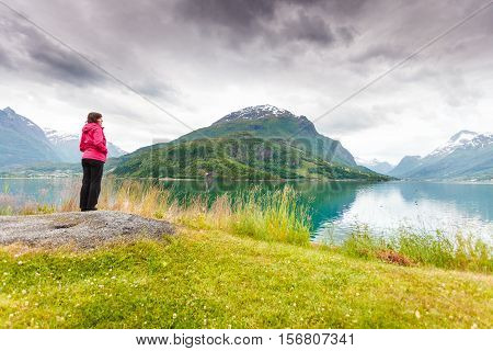 Travel concept. Mature tourist woman on sea shore looking at fjords beautiful landscape in Olden village Sogn og Fjordane county Norway.