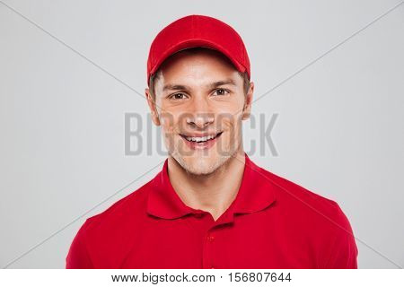 Close up courier. front portrait. smiling man. looking at camera. isolated gray background