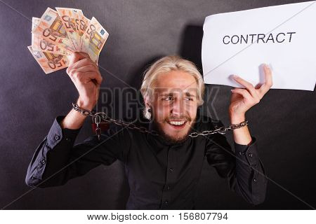 Man With Chained Hands Holding Contract And Money