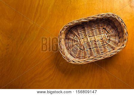 Woven wicker basket on wooden background sample