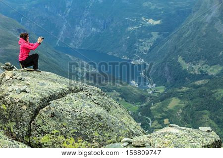 Tourism vacation and travel. Female tourist taking photo with camera enjoying Geiranger fjord and mountains landscape from Dalsnibba Plateau viewpoint Norway Scandinavia.