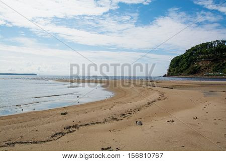 Not long sandy spit in the sea bay. Sandy beach and green rock.