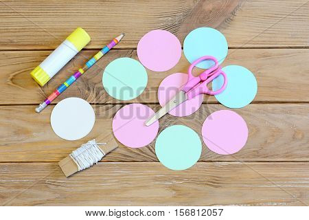 How to make a colored paper Christmas ball ornament. Step. Circles cut from colored paper, scissors, pencil, glue stick, cardboard template, ribbon on a wooden table. Christmas children art. Top view
