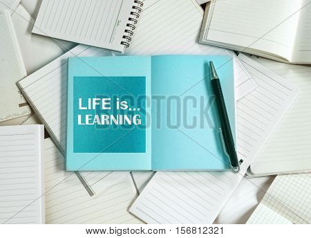 Many empty notebook papers and note pads background with one blue book and life is learning quote