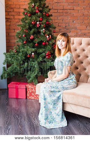 holidays, x-mas, winter, happiness concept - smiling woman near the christmas tree.
