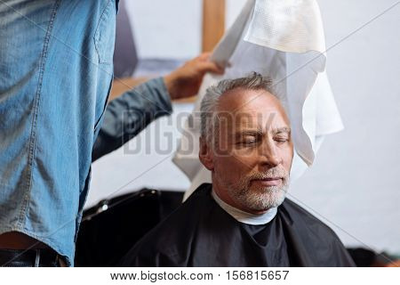 Wiping dry. Portrait of satisfied old man during wiping his hair in barber shop by special towel.