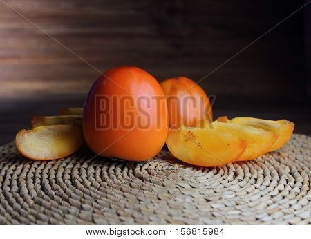 fresh persimmon and persimmon slices on a straw napkin