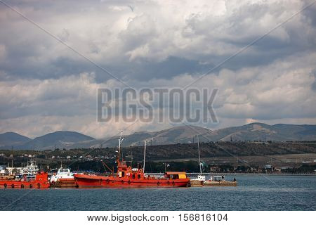Red Vessels near the mooring, cloudy landscape