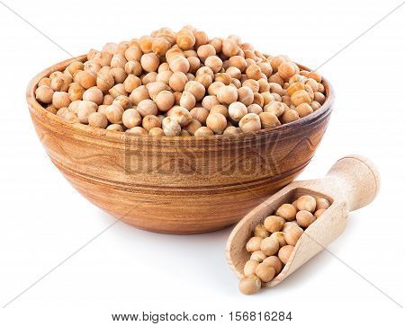 Dry chickpeas in clay bowl with wooden scoop near isolated on white background. Uncooked chick-pea. Chickpea grains