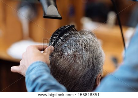 Final steps. Close up portrait, male hairdresser combing and blow drying the hair of senior client at barber shop.