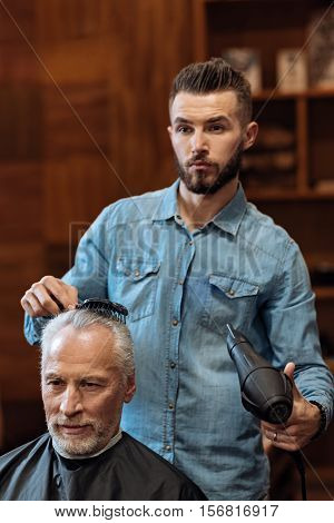 Im so fancy. Young handsome bearded hairstylist holding comb and blow dryer while standing near his senior client and looking forward.