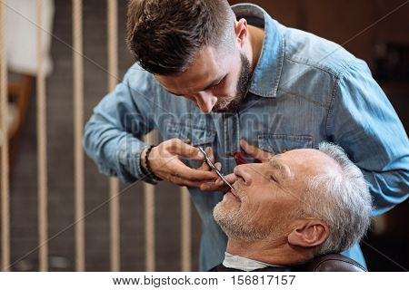 Fussy work. Side view of concentrated bearded hairdresser cutting mustache of nice smiling senior client at barbershop.