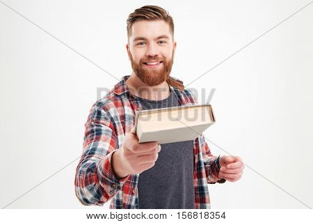 Portrait of a smiling bearded guy in plaid shirt giving book to camera over white background