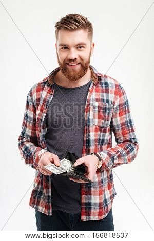 Smiling happy bearded man in plaid shirt putting money in his wallet over white background