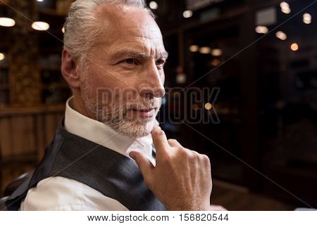 Thinking about future. Close up portrait of attractive thoughtful senior man holding his finger on chin while looking forward.