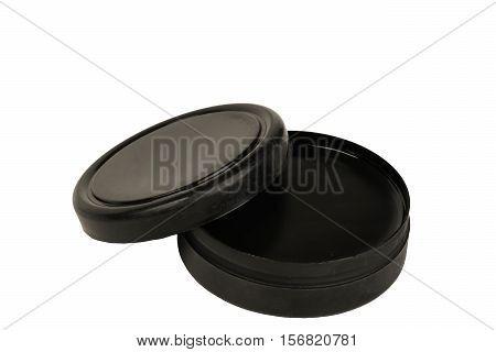 black shoe polish lid ajar on a white background
