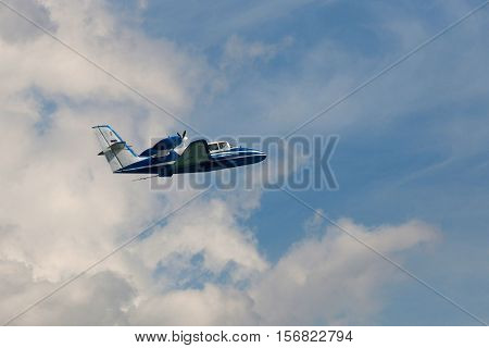 Flying amphibian aircraft in a cloudy sky