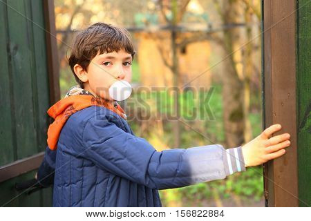 preteen handsome boy with chewing gum bubble close up country portrait