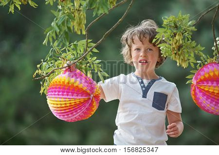 Boy with colorful lampion in summer at a party