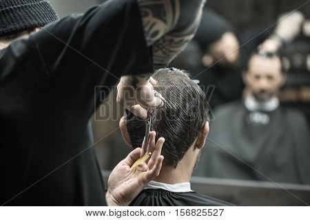 Heedful barber is cutting the hair of his client in the black cape in the barbershop. He wears a black T-shirt with a black cap and has a hair comb and scissors. They blurry reflected in a mirror.