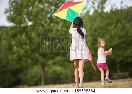 Two happy girls flying a kite together in the nature